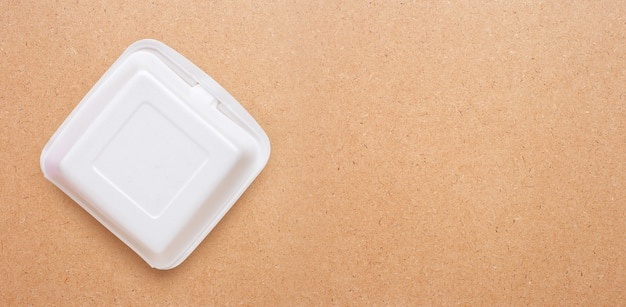 Foam food container on plywood background.