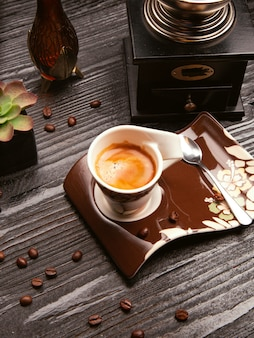 Foam milky cappuchino, latte in decorative cup and brown plate with metallic spoon.