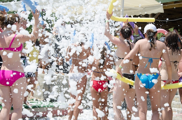 Foam party on the beach. people dance to music with foam