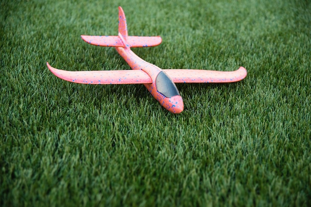 Foam plastic plane. child toy airplane on green grass. active outdoor games. copy space.