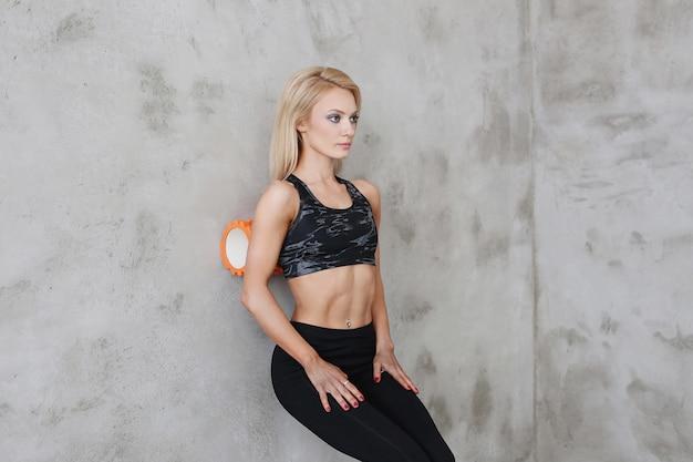 フォームローラーエクササイズ、筋肉質のアスリート女性のワークアウト