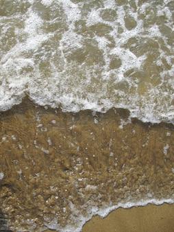 Foam on a sandy beach, waves in the ocean