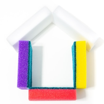 Foam sponges for washing dishes folded in the shape of a house with a roof