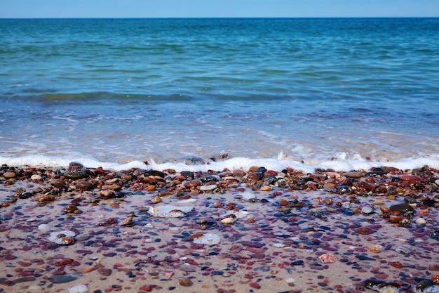 자갈이 있는 모래 해변에서 거품 서핑.