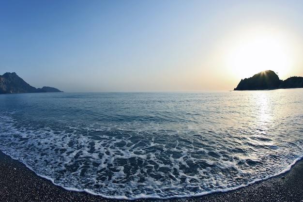 夜明けのビーチで泡の波