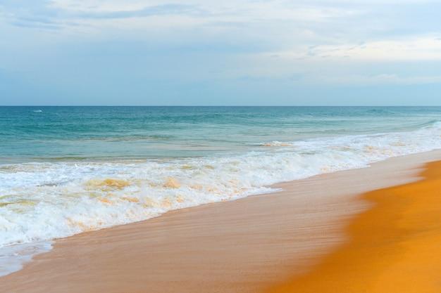 Foam wave, running on the sandy shore.