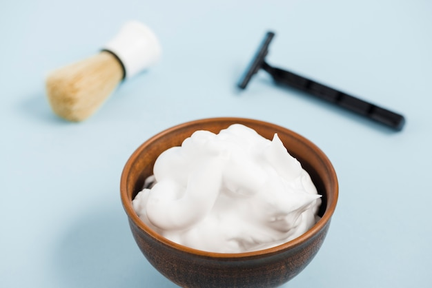 Foam in wooden bowl in front of razor and shaving brush against blue background