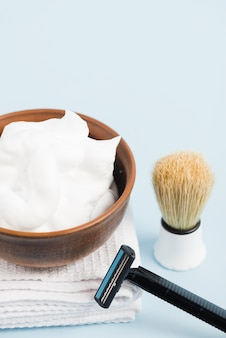 Foam in wooden bowl on white folded towel with shaving brush and razor against blue background
