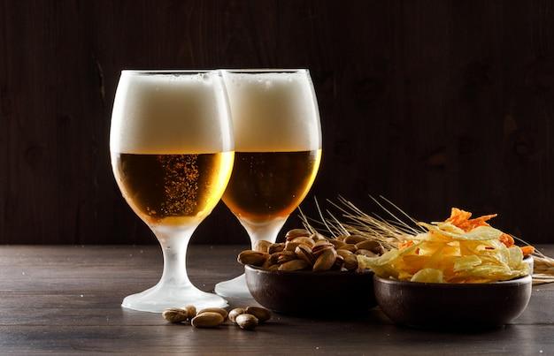 Пенное пиво с фисташками, колосья пшеницы, чипсы в бокалы на деревянный стол, вид сбоку.