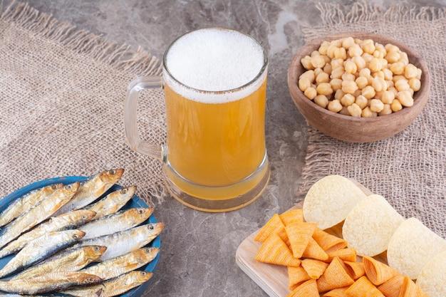 Пенное пиво и ассортимент закусок на мраморной поверхности. фото высокого качества