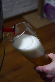 Пенное пиво наливают из пивной бочки через кран в стеклянный бокал.
