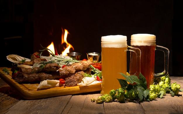거품이 많은 맥주. 두 맥주 잔과 나무 테이블에 구운 고기.