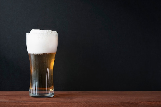 Foamy cold beer in glass beer mug on wooden table in a pub. dark black wall as background for text, menu, mockup