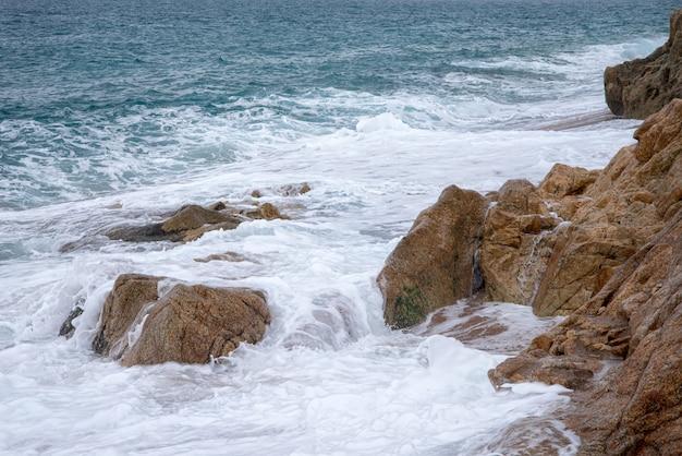 Foamy sea waves break on coastal stones