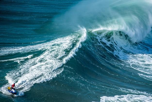 Пенистые волны атлантического океана с райдером на гидроцикле