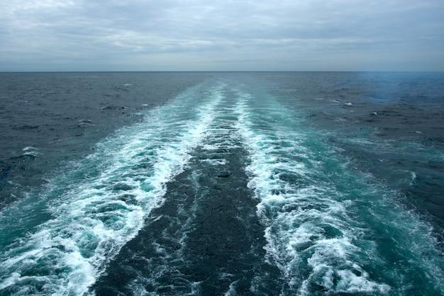 クルーズ船の後ろの水面に泡の波