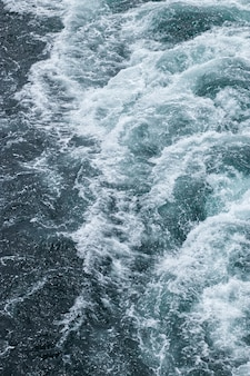 Foamy waves on the surface of the water behind the cruise ship