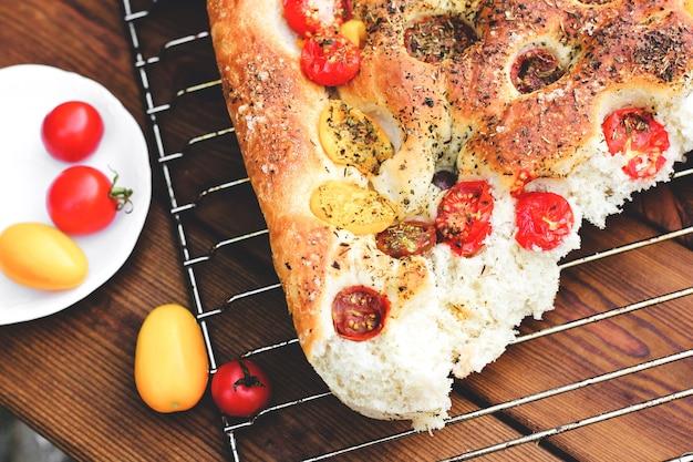 フォカッチャ。イタリアンブレッド。トマトのパン。手作りの料理。家で料理する。ワイヤーラックの焼きたてのパン