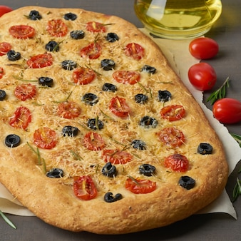 Focaccia, pizza, italian flat bread with tomatoes, olives and rosemary on brown table