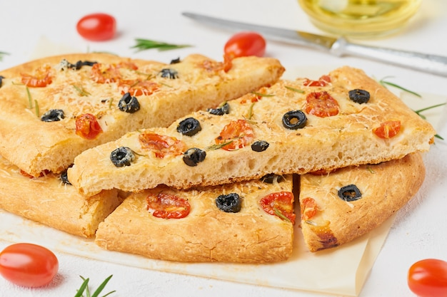 Focaccia, pizza, italian flat bread with tomatoes, olives and rosemary, side view