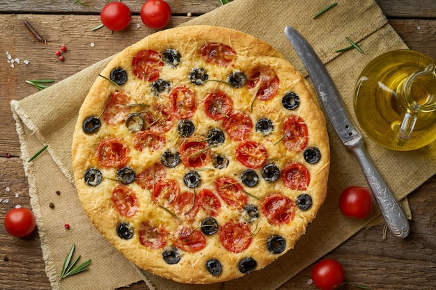 Focaccia, pizza, italian flat bread with tomatoes, olives and rosemary on wooden rustic table