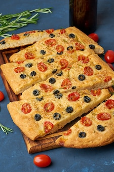 Focaccia, pizza, italian flat bread with tomatoes, olives and rosemary.