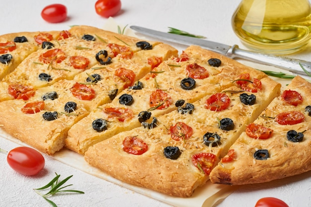 Focaccia, pizza with tomatoes, olives and rosemary. chopped italian flat bread. side view