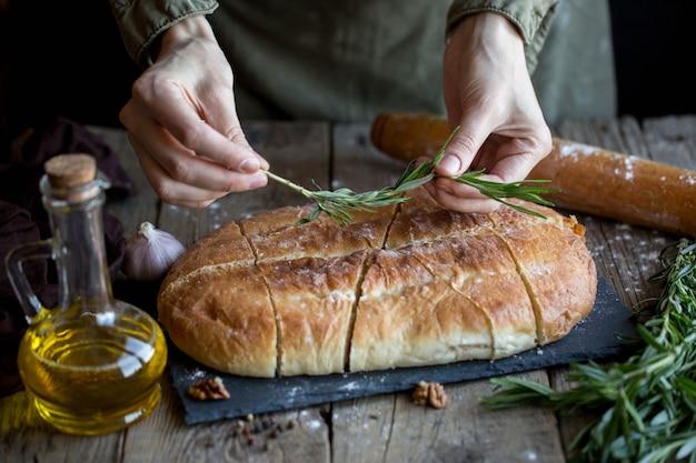 バターと塩のフォカッチャ。ホステスのテーブルの上の美しいフォカッチャ。