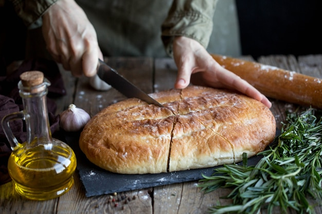 Focaccia with butter and salt. focaccia on a cutting board with herbs and spices.