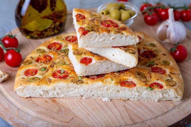 토마토와 올리브와 함께 포카 치아. 전통적인 이탈리아 빵. 수제 베이킹. 클로즈업, 선택적 초점.