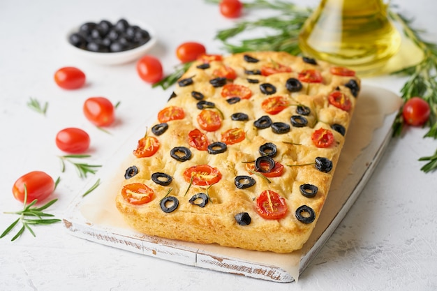 Focaccia with tomatoes, olives and rosemary. traditional italian flat bread