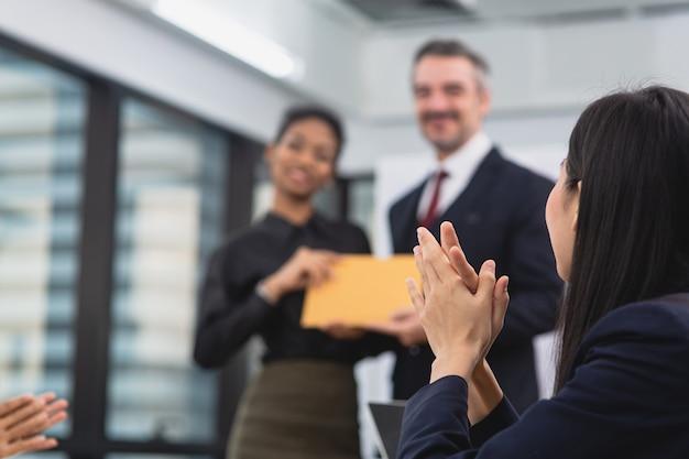 아시아 비즈니스 여성의 손에 집중하고 사무실 회의실에서 아프리카 및 고위 동료에게 박수를 치고 성공을 축하합니다.