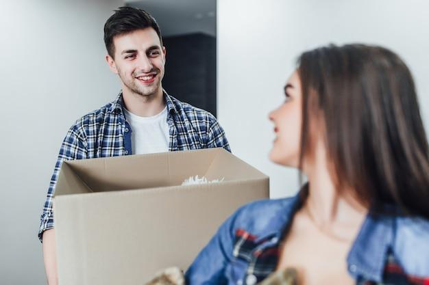 新しい家の手にボックスを持つ幸せな男に焦点を当てる