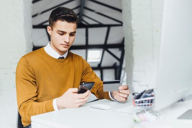 Сосредоточьтесь на мужчине, он держит телефон, а на его столе три визитные карточки, он рабочий. поиск информации.