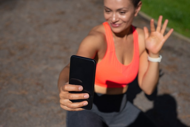 Focus on black smartphone in a smiling woman's hand sitting on a running way