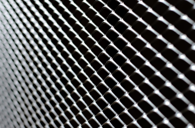 Focus and blurred of dark gray and silver grid of metal fence
