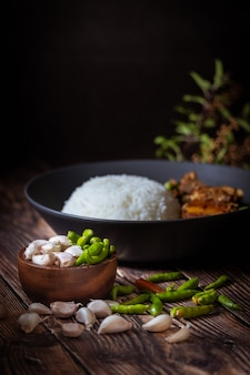 Focus chilli pepper and garlic, thai food, rice topped with stir fried basil and pork bone.