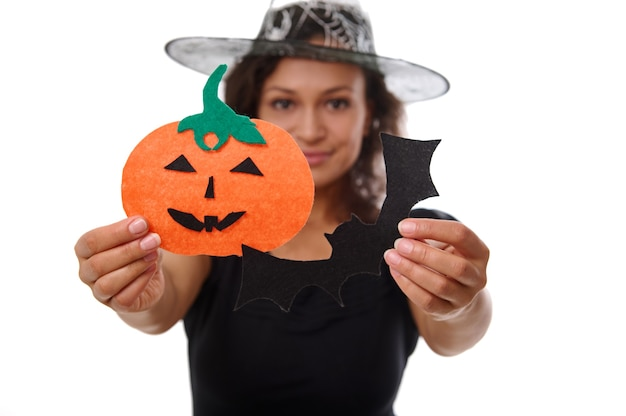 Focus on cut felt handmade pumpkin and bad in the hands of a blurred beautiful woman dressed in witch carnival costume isolated on a white background with copy space for halloween advertisement