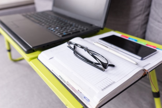 Focus on glasses lying on the laptop table near open blank page of a diary with a pen for making appointments, organising a schedule