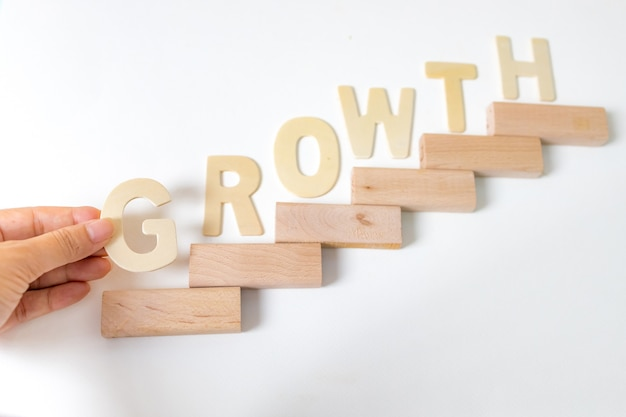 Focus of hand arranging wood block stacking as step stair. business concept for growth success process. stairs up as a symbol of career growth up or business success. the word written the growth.