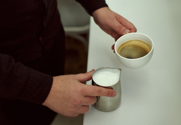 Focus on hands of baristas holding in one hand a cup of coffee, and in the other milk