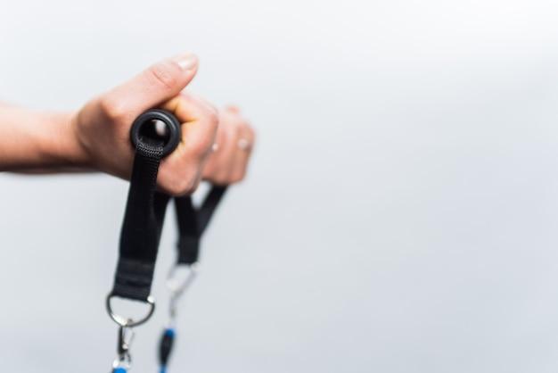 コピースペースのある白い背景にエクササイズロープをキャッチする手を集中させます。運動とフィットネスの女の子の概念。