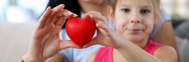 Focus on hands of happy mother and little daughter hands holding toy red heart. love relationship between mum and child.