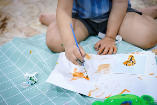 Focus on  hands on paper. children use paintbrushes to paint watercolors on paper to create their imagination and enhance their learning skills.