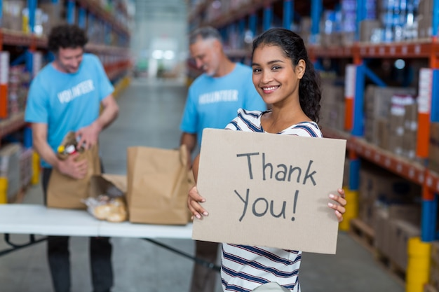 Focus of happy volunteer posing and holding a sign