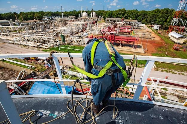두께 저장 오일 및 가스 탱크의 남성 작업자 로프 접근 높이 안전 검사에 중점을 둡니다.