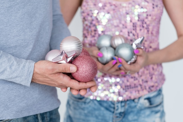 Focus on man holding handful of rose gold glittery baubles. woman in the holding silver spheres.