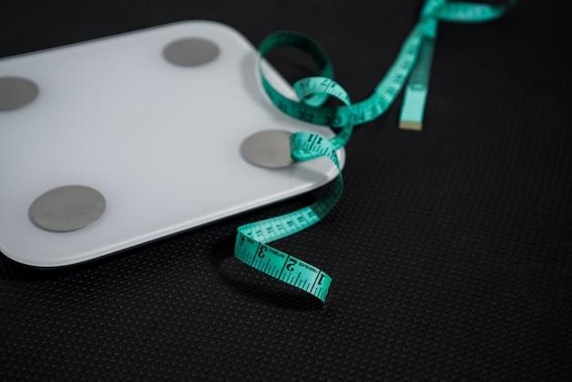黒の背景に巻尺と電気スケールに焦点を当てます。重量を失うという概念。