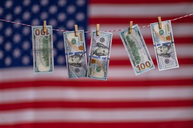 Фокус долларовых банкнот, висящих на веревке на фоне американского флага. финансовый кризис