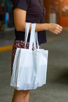 Фокус белой ткани сумки и азиатские женщины.